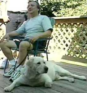 Blind owner seated with dog Dorado at foot